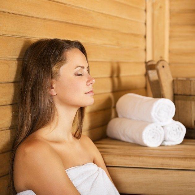 Frau mit Handtuch entspannt in Sauna